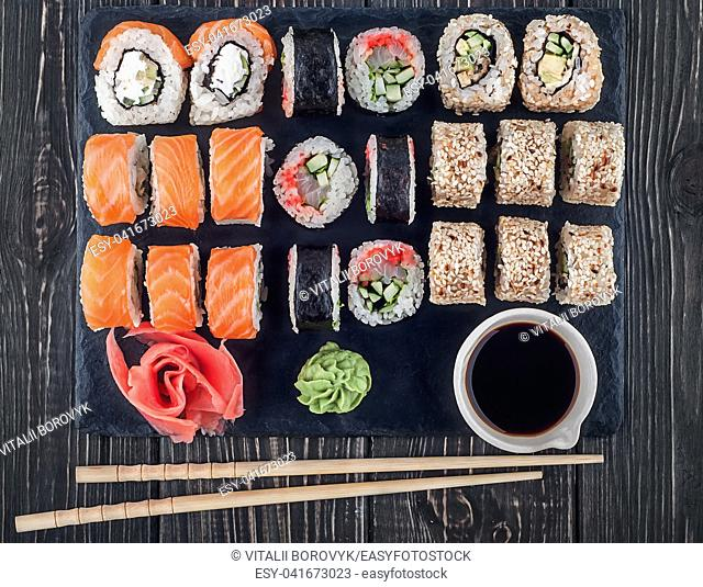 Various sushi rolls on slate. Roll Philadelphia, California and Lollo Ross with wasabi ginger and soy sauce. Top view
