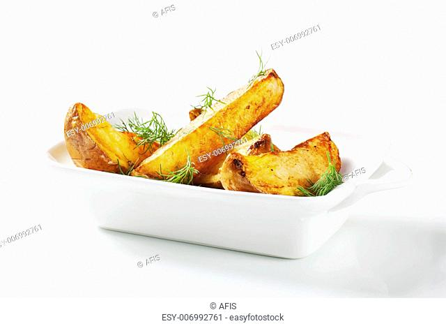 Roasted potato wedges garnished with fresh dill