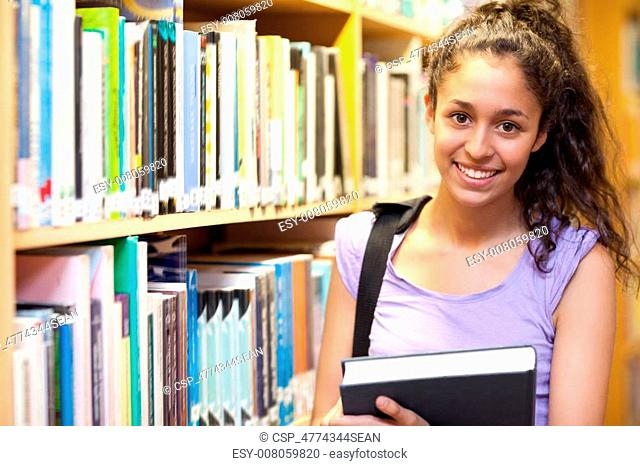 Smiling female student posing with a book