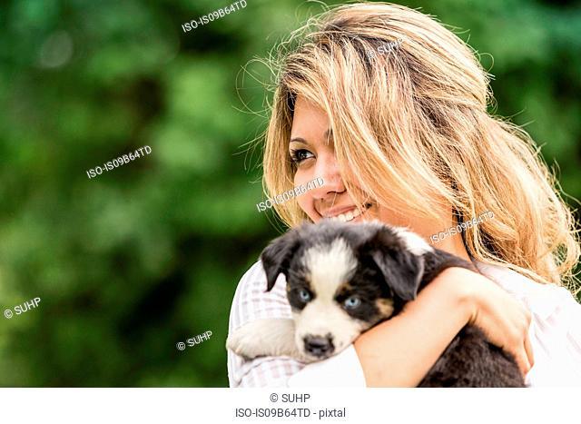 Young woman holding sheepdog puppy on ranch, Bridger, Montana, USA