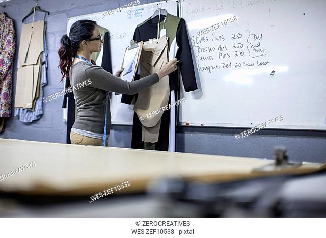 Fashion desiger in clothing factory checking work on clipboard
