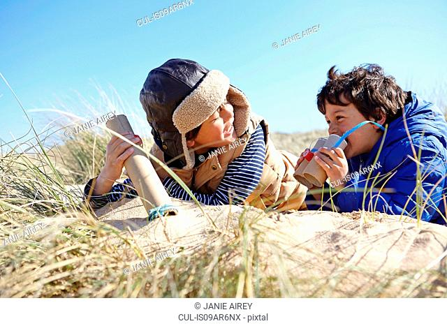 Two young boys on beach, holding pretend binoculars