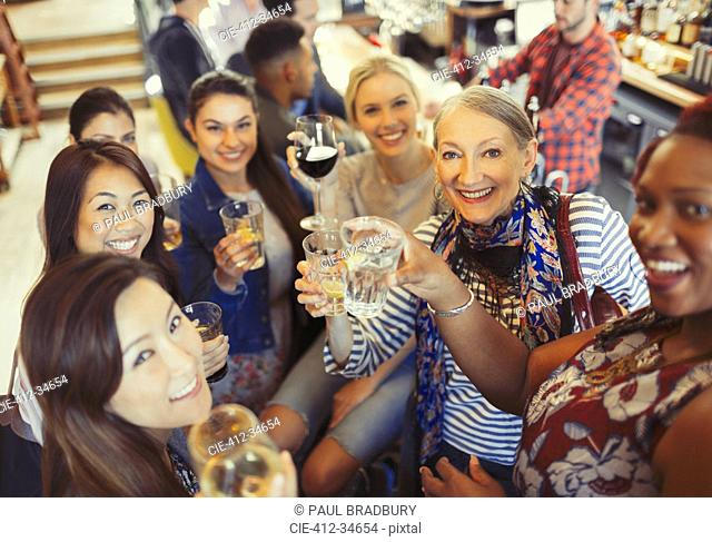 Portrait smiling, confident women friends toasting beer and wine glasses at bar