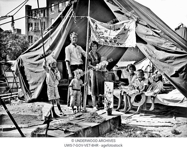 Wahington D.C.: July, 1932. A World War I veteran from Charleston, South Carolina, with his wife and seven children standing before their tent at the Bonus...