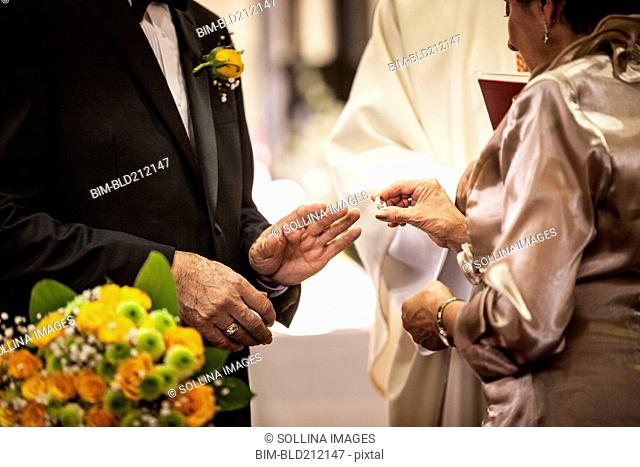 Senior couple exchanging rings at wedding