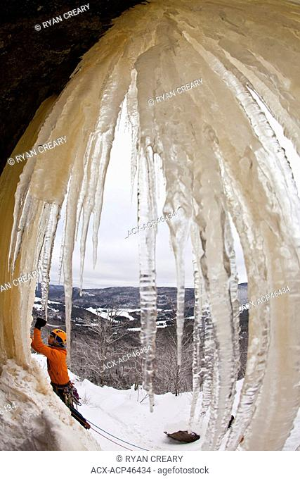 A man climbs a steep, colorful ice climb, Aurorae WI 4+, near St. Raymond, Quebec, Canada