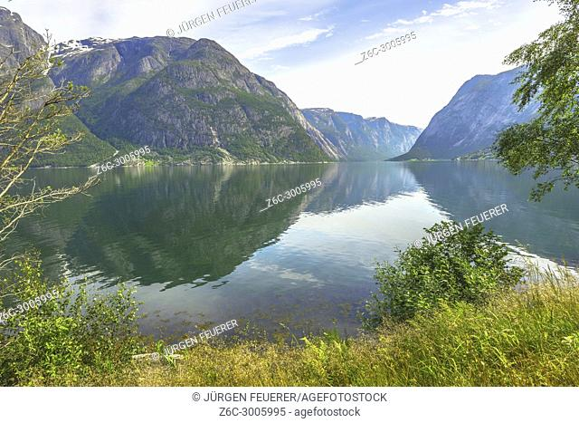 The Eidfjorden with reflections near village Eidfjord at the seashore on the right, Norway, Scandinavia, view to Simadalsfjorden
