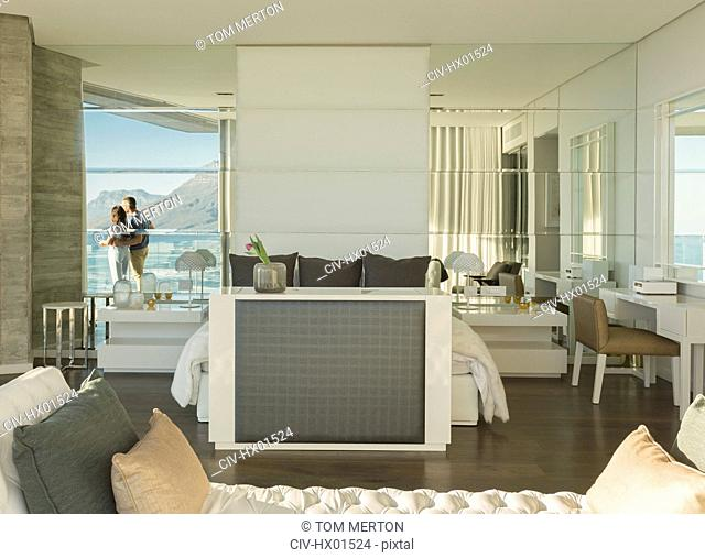 Reflection of couple looking at sunny ocean view from modern luxury home showcase bedroom balcony