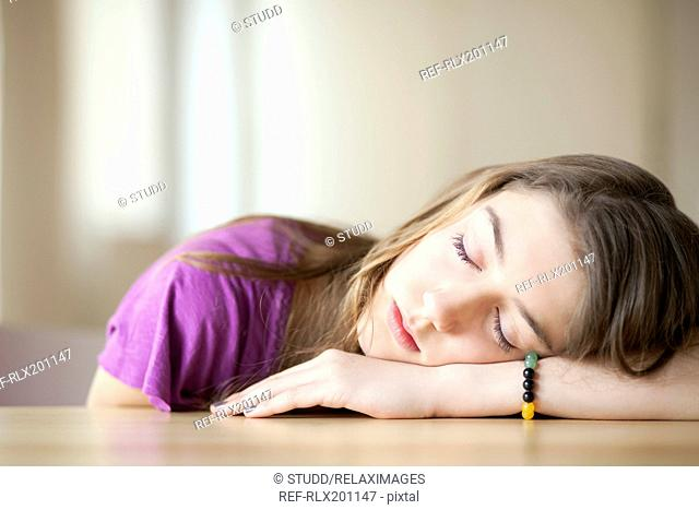Girl sitting at table with eyes closed