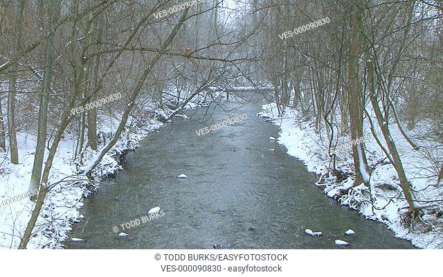 Creek in winter with snow falling