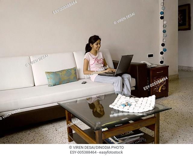 Young girl operating laptop sitting on sofa MR477