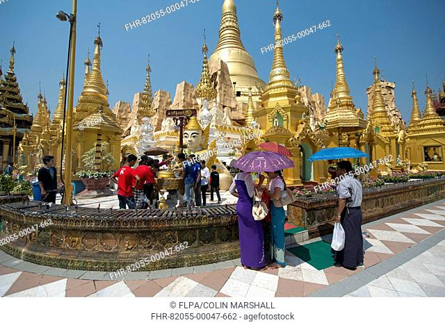 People with umbrellas at Buddhist gilded pagoda and stupa, Shwedagon Pagoda, Yangon, Myanmar, March