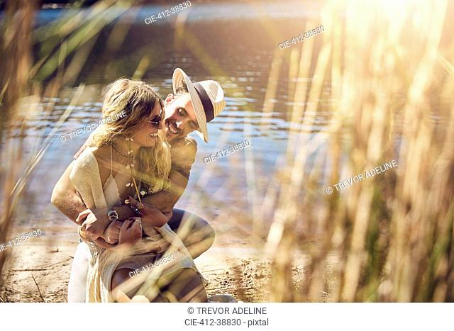 Affectionate young couple hugging at sunny summer riverside