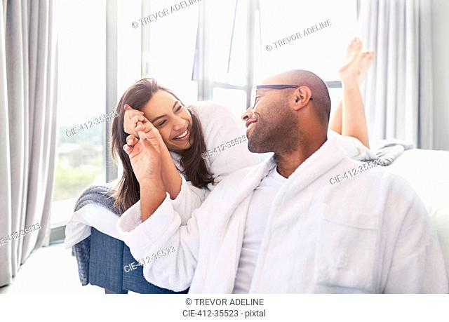 Affectionate couple holding hands in bedroom