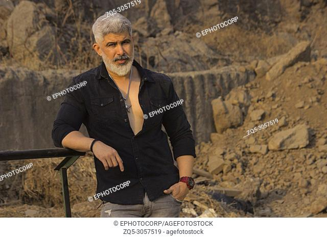 Man with white hair and beard in black shirt looking at camera against a rock background