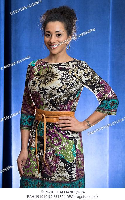09 October 2019, Saxony, Dresden: Nadja Benaissa, former singer of the German girl group No Angels, stands in front of a blue curtain in the boulevard theatre