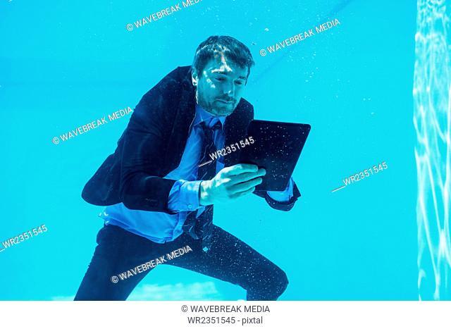 Businessman using tablet underwater