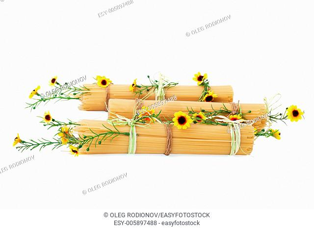 Uncooked Italian spaghetti decorated with yellow flowers isolated on white background