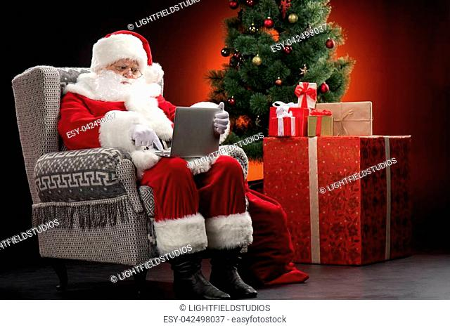 Santa Claus sitting on grey armchair using laptop and pointing