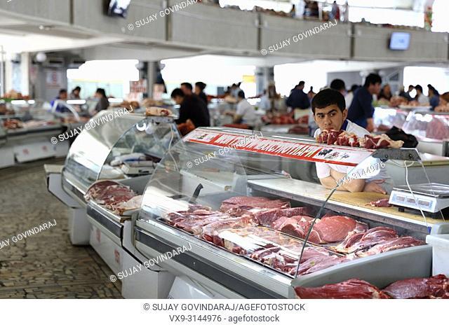 Tashkent, Uzbekistan - May 01, 2017: Unknown meat seller sits idle at meat pavilion in Chorsu market