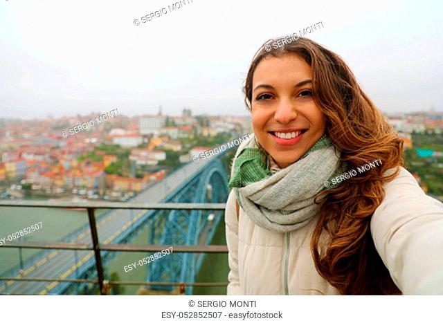 Happy young woman take selfie photo with Porto Cityscape on the background in winter time. Self portrait of beautiful girl in Porto, Portugal