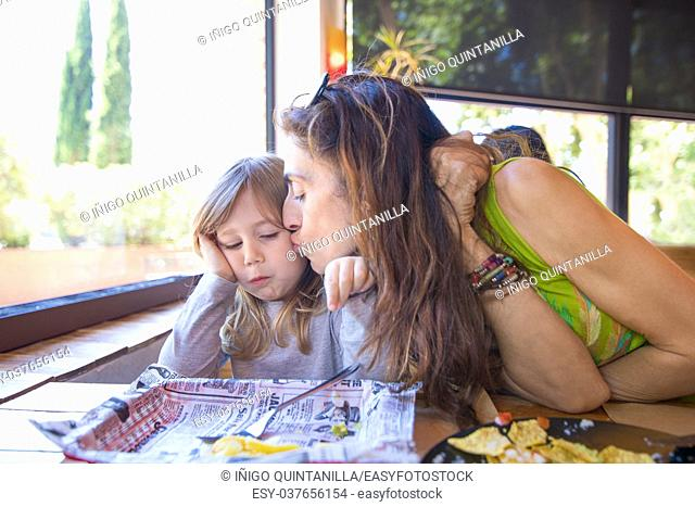 Tender scene. Woman mother kissing her three years old blonde daughter, a child eating, sitting in a restaurant next to window. Summer