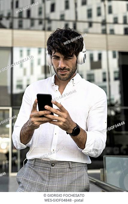 Young man with headphones and cell phone in the city