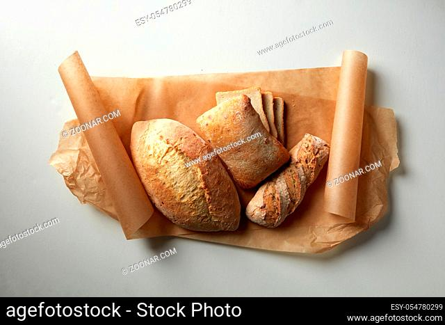 Different kinds of bread represented over cooking paper over white background. Range of different sorts of bread for your choice