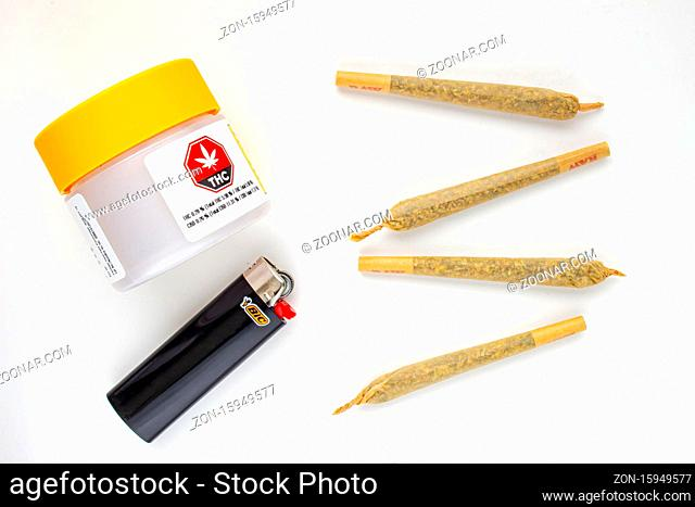 Calgary, Alberta, Canada. Aug 19, 2020. A Cannabis white and yellow plastic packaging container with Cigarettes, Prerolls or Joints and a lighter on a white...