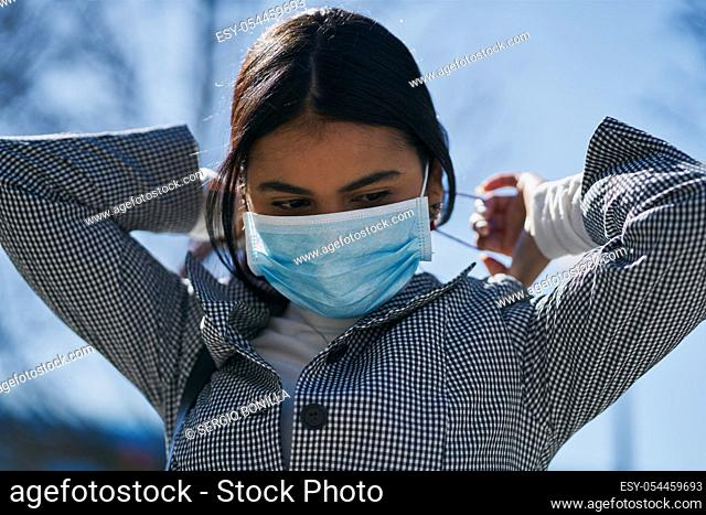 Girl putting on a protective mask to avoid contagion while walking down the street. Coronavirus concept
