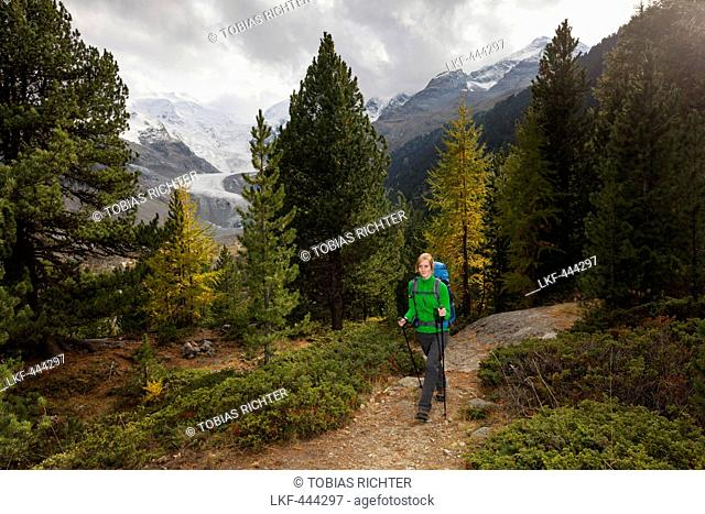 Young woman with backpack hiking in Morteratsch Valley, Bernina Range in background, Engadin, Canton of Grisons, Switzerland