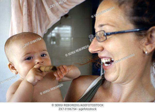 Woman with her baby smoking a fake cigar, Cuba