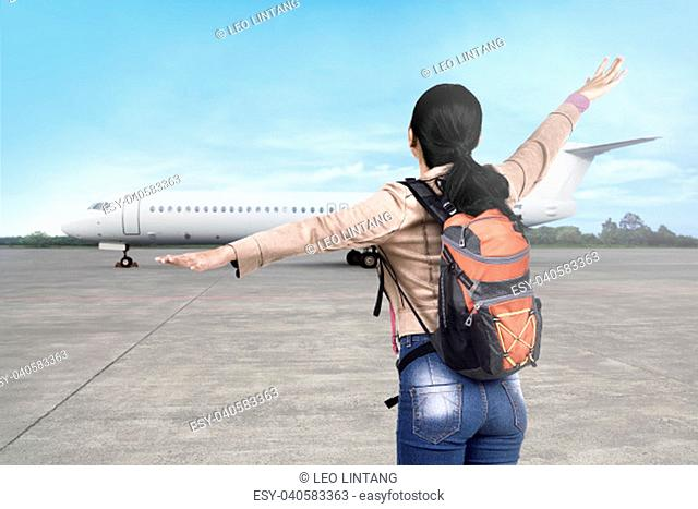 Happy asian tourist woman going traveling by airplane on the airport