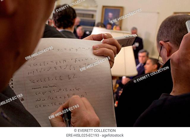 A reporter takes shorthand notes while President Barack Obama and Prime Minister Gordon Brown of the United Kingdom speak to the press in the Oval Office March...