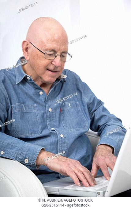 Senior man using and writing on a white laptop computer