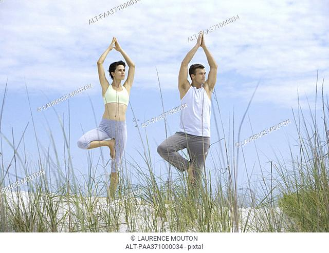 Couple standing in yoga tree pose on beach