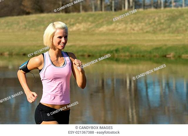 Young woman jogging water park in summer