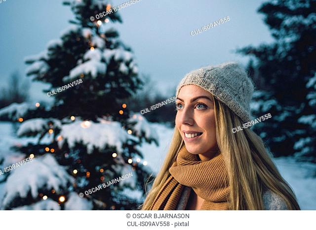 Portrait of young woman wearing woollen hat and scarf by illuminated christmas tree looking away smiling