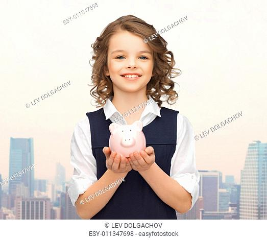 people, money, finances and savings concept - happy girl holding piggy bank on palms over city background