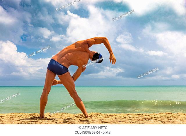 Rear view of muscular male swimmer on beach bending over sideways