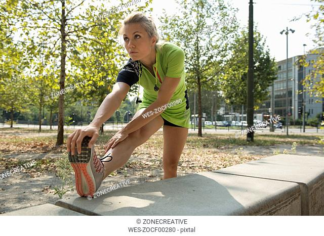 Female athlete stretching in urban park