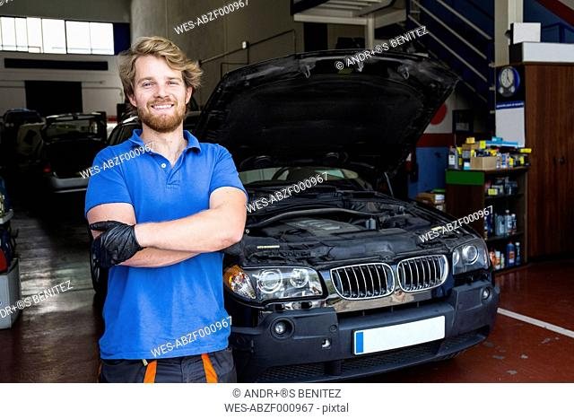 Confident mechanic standing in his car workshop with arms crossed