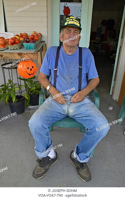 Man sits in chair in front of small vegetable and produce store in central Georgia in Southeast USA