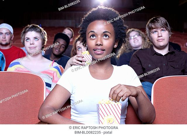 African woman eating popcorn in movie theater