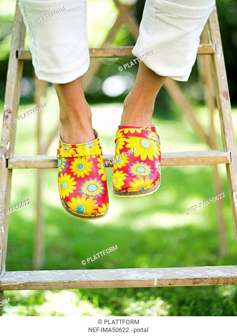 A woman wearing flowery clogs sitting on a ladder, Stockholm, Sweden