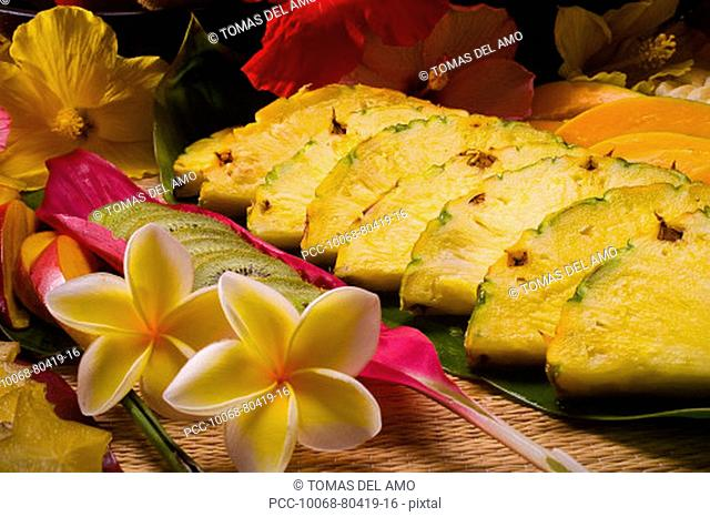 Studio shot of a variety of tropical fruit cut into slices, with flowers