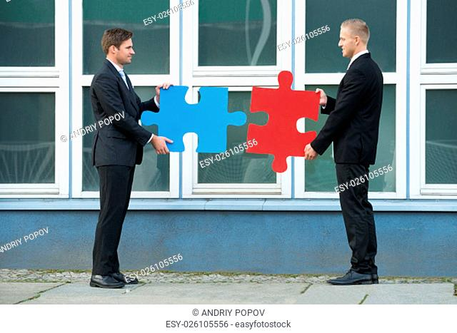Side view of businessmen joining jigsaw pieces while standing outside office