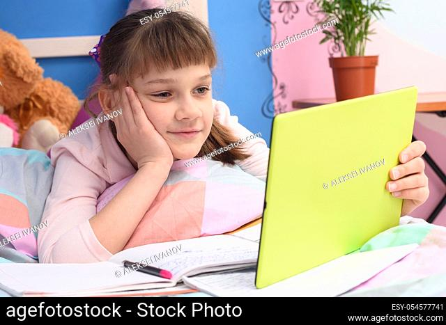 The girl lies in bed and looks at the tablet video tutorials
