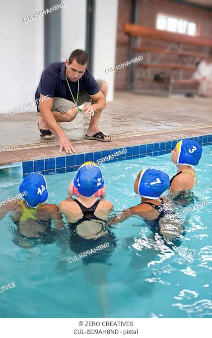 Four schoolgirl water polo players listening to teacher poolside