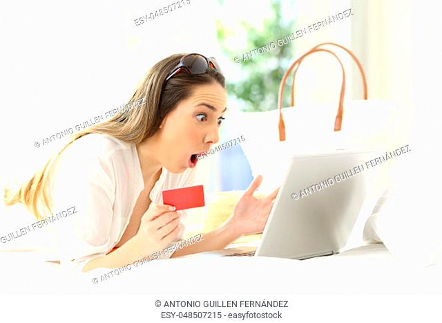 Amazed woman buying on line lying on a bed in an hotel rrom in summer vacations